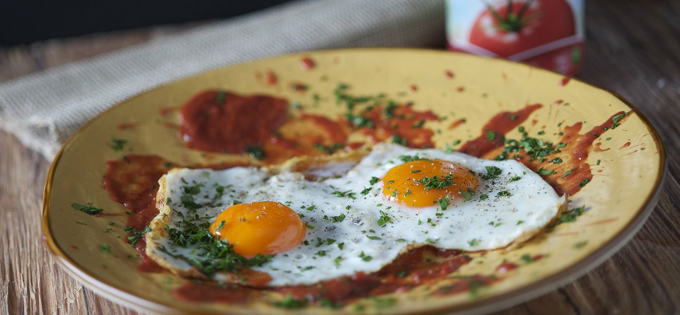 Fried egg sunny side up with tomato